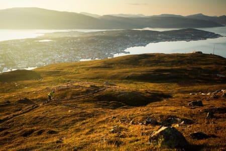 Stien går fra toppen Bønntua ned til Fjellheisen (til høyre i bildet) for så å traversere tilbake og ned til Tromsø. / Stisykling i Norge.