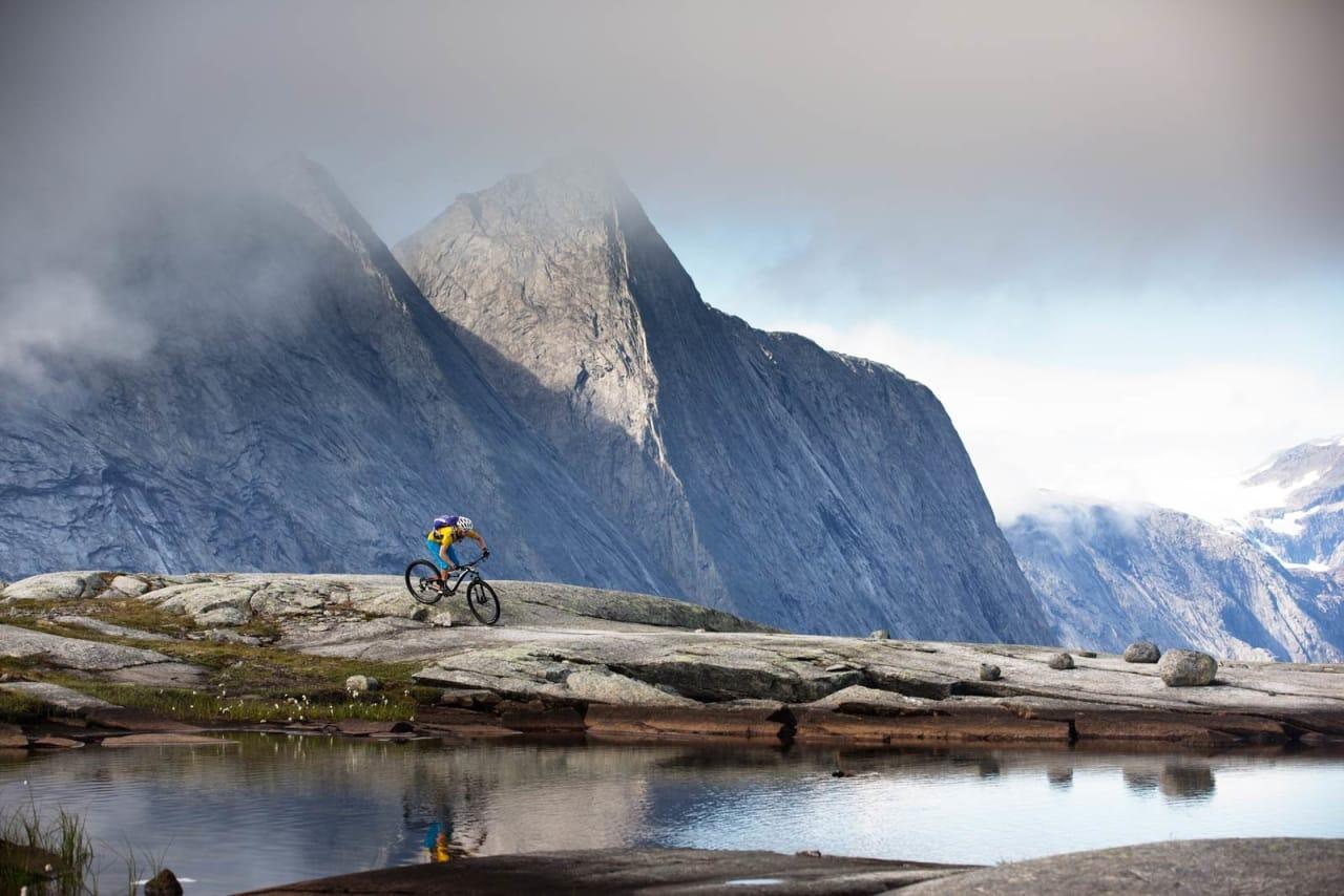 Per-Eivind Syvertsen sykler blant helt andre omgivelser enn han er vant til fra hjembyen Kongsberg. Isbreen Frostisen skimtes såvidt i bakgrunnen. / Stisykling i Norge.