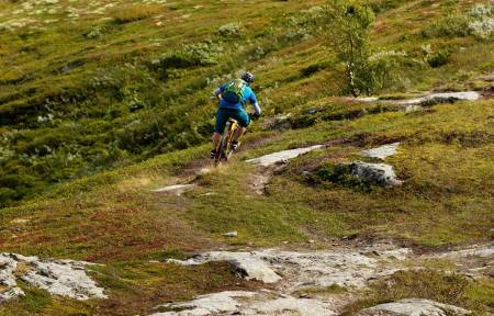 Arne Radmann slipper opp ned fra Svarthaugen mot dalbunnen. / Stisykling i Norge