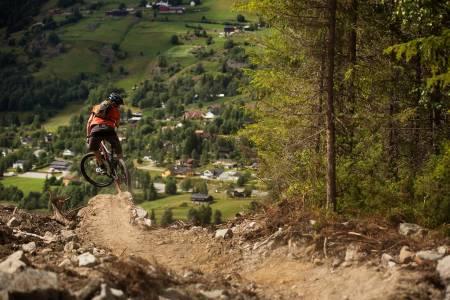 Vegard Breie får luft under hjulene på vei ned mot hjembygda Ål, på stien han selv har bygget og gitt navn til. / Stisykling i Norge.