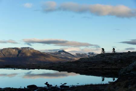 En tur over Molden er ekstra fint på en klarværsdag, hvor du kan se langt innover fjellene mot blant annet Hurrungane. Andreas Køhn og Knut Myking går i ett med landskapet. / Stisykling i Norge.
