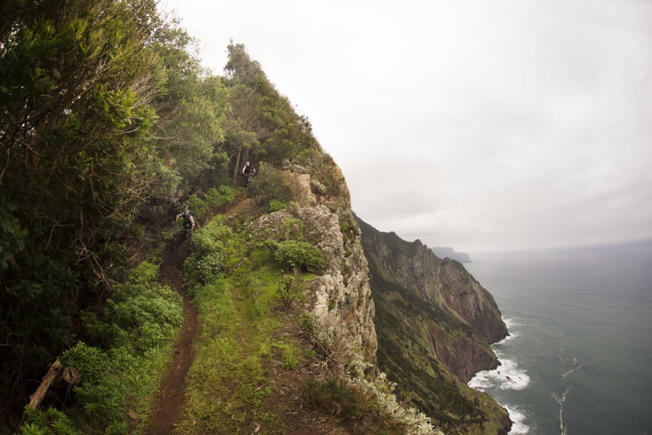 PÅ KANTEN: Madeira er en opplevelse i seg selv, med eller uten sykkel. John Fernandes leder Knut Lønnqvist ned en sti langs et stup på nordsiden av øya. Med storslagen natur blir det hyppige stopp for å ta omgivelsene inn over seg. Foto: Kristoffer Kippernes