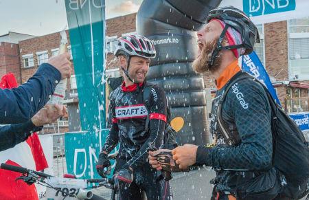 Erik Skovgaard Knudsen og Per Thomsen tok seg et bad i champagne etter å ha syklet 70 mil over Finnmarksvidda. (Foto: Venche Jensen)